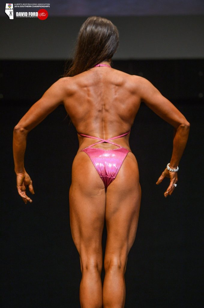 Dr. Mandy showing back muscles in a competition