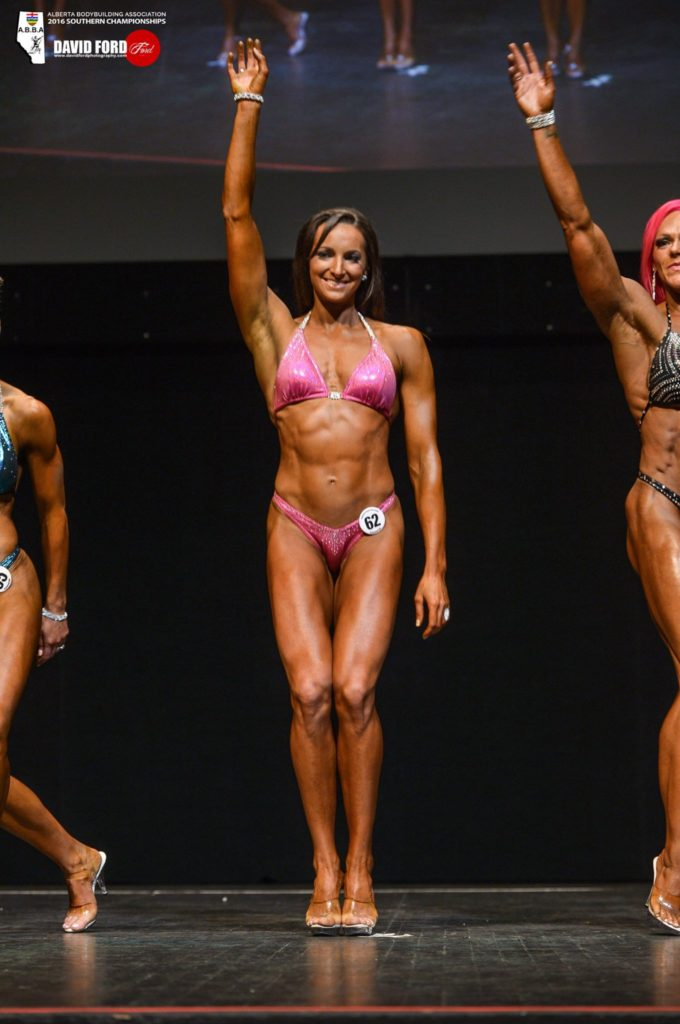 Dr. Mandy in a bodybuilding competition waving
