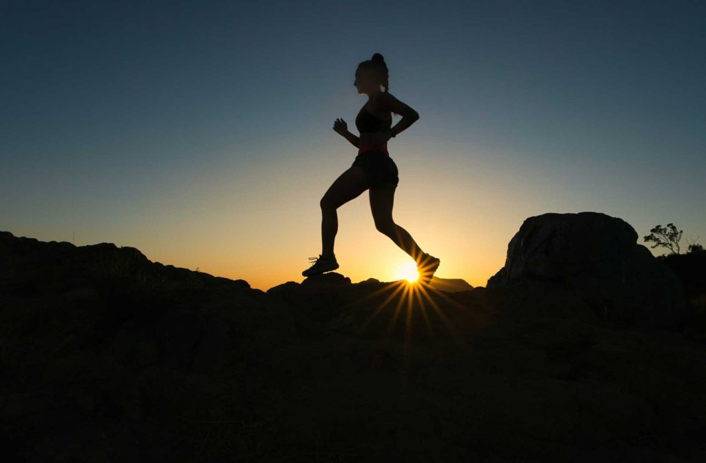 Silhouette of active woman running outdoors at sunset