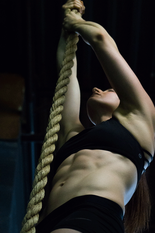 Fit woman rope climbing at the gym with abs