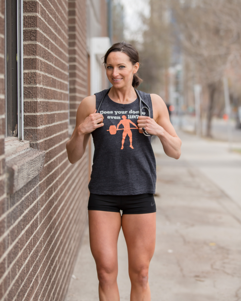 Naturopathic doctor athletic performance expert posing outside by a brick wall